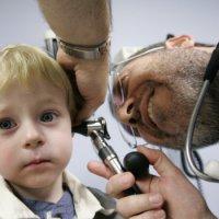 Врач проводит осмотр уха ребёнка с целью диагностики